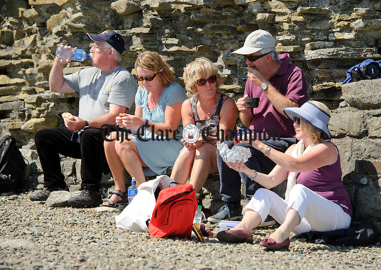 Visitors take a break for lunch during a trip to Scattery Island as part of the Kilrush Traditional Music and Set dancing Festival. Photograph by John Kelly.