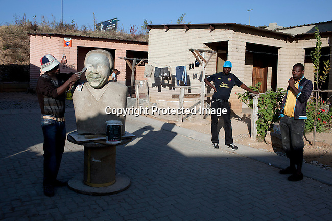 ALEXANDRA TOWNSHIP, JOHANNESBURG, SOUTH AFRICA : Artist George Rangwanasha makes a Mandela sculpture outside his home in Alexandra, a poor township in Johannesburg, South Africa. (Photo by Per-Anders Pettersson)