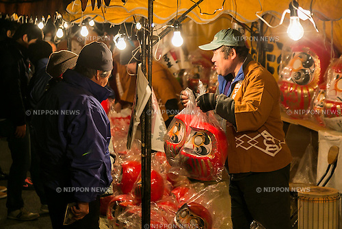 A merchant sales Daruma dolls outside the Shorinzan Daruma Temple in Takasaki City, Gunma Prefecture on January 6, 2016, Japan. Every year thousands of people visit the country's most famous Daruma market (Daruma ichi) held at the Shorinzan Daruma Temple on January 6 and 7. Takasaki City, is known as the capital of Daruma dolls and about 80% of Japan's Daruma are produced there. According to the tradition, Daruma dolls are sold without pupils painted on their eyes. People color in one pupil when a wish is made or a goal set, and when the wish comes true or the goal is achieved they fill in the other pupil. At the end of the year, used Daruma dolls are returned to the temple to be burned. (Photo by Rodrigo Reyes Marin/AFLO)