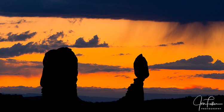 Balanced Rock in Arches National Park, near Moab, Utah in silhouette with orange sunset skies and virga streaking down from the clouds.