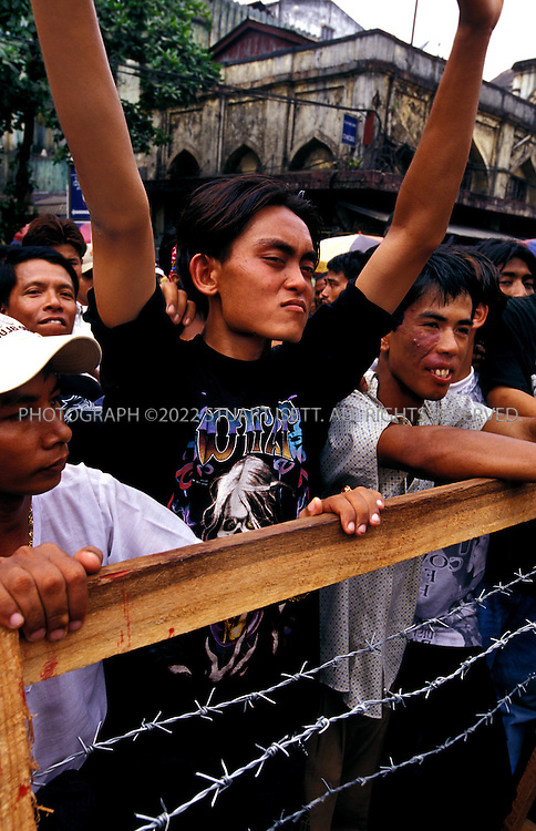 4/12/2002--Rangoon, Burma..Rock fans dance and rock behind barbed wire across the Aung San Market...The annual outdoor free concerts are held every April duirng Burma's traditional New Year celebrations. Normally gatherings of young men woiuld be broken up by Burma's ruling junta but the concerts are the one time of year such large gatherings are allowed. Local authorities are nervous that such concerts may turn political or violent and watch the shows carefull for signs of unrest...All photographs ©2003 Stuart Isett.All rights reserved.