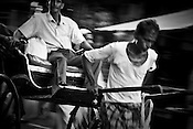 A rickshaw puller meanders through the traffic  in Calcutta, India. 93 out of every 100 rickshaw pullers are homeless. They sleep after the city sleeps and wake up before everyone else does. Many of them are the sole bread earners for their family. Many plus 40. Many minus any other specialisation for any other job. Of the twenty four thousand rickshaw pullers, only 387 have licenses. .Many rickshaw pullers earn a meagre wage of 100-150 rupees (US $ 2.25-3.5) a day of which they have to give a daily rickshaw rent of 60 (US$ 1.35) rupees to the agent at the end of the day.