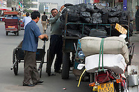 Man delivering coal from a heavily loaded motor tricycle in Datong, Shanxi, China.