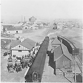 D&amp;RG passenger train stopped at new Monte Vista depot.  A crowd of passengers and well wishers have gathered.  Horse-drawn wagons and three very early automobiles are present.<br /> D&amp;RG  Monte Vista, CO  ca. 1907-1909