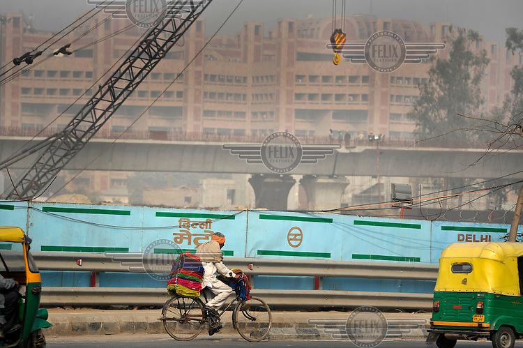 A man rides on a bicycle next to a building site for a new major road being constructed for the 2010 Commonwealth Games.