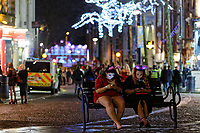 Pictured: Two young women sit on a bench check their mobile phones. Sunday 31 December 2017 and 01 January 2018<br /> Re: New Year revellers in Wind Street, Swansea, Wales, UK