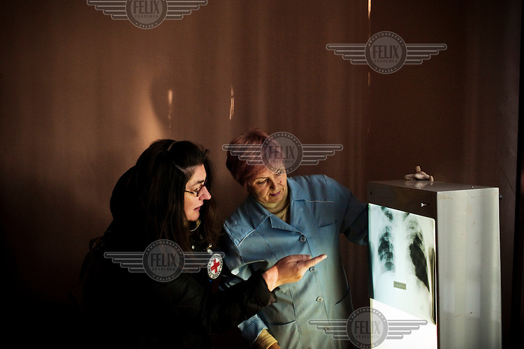 A woman from ICRC (International Committee of the Red Cross) inspects an X-ray machine funded by the ICRC at Specialised Prison Colony 27. Kyrgyzstan's prisons are experiencing a TB epidemic, where the incidence rate is estimated at 25 times higher than in civil society.