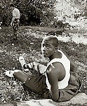 A seventeen year-old sits on the shoulder of Holton Street in Tallahassee, Florida  while crack-squad Officer Mark Peavy searches for drugs he saw James throw during a foot chase.  Peavy found marijuana and James was arrested on a possession charge.  Seven days later the suspect was charged with an Oct 11, 1985 crack-related murder at the campus Highlands Apartments at 2501 Meridian Street in Tallahassee.