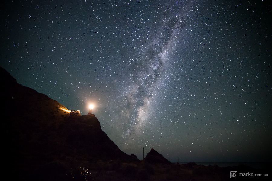 Cape Palliser Lighthouse on the south eastern tip of the North Island of New Zealand, lights up the surrounding landscape as the Milky Way shines ever so brightly behind.