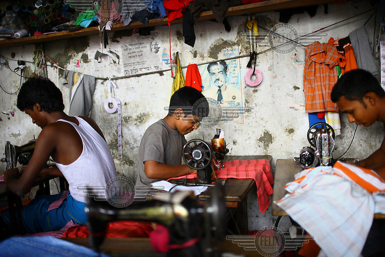 Eleven-year-old Bellal (centre) sews clothes in  a factory in Dhaka. Working for 12 hours a day he is paid less than GBP 9 per month.