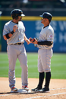 Louisville Bats outfielder Ryan LaMarre (10) gives his gloves to first base coach Eugenio Suarez (7) during a game against the Buffalo Bisons on May 2, 2015 at Coca-Cola Field in Buffalo, New York.  Louisville defeated Buffalo 5-2.  (Mike Janes/Four Seam Images)