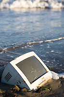 Disgarded obsolete broken computer monitor left abandon on public beach