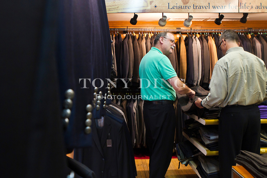 """Hank"" of The Van Boven Shop, left, advises on shades of a sports jacket a father is looking for to gift his U of M son, Friday, Sept. 2, 2011 in Ann Arbor, Mich. (Tony Ding for The New York Times)"