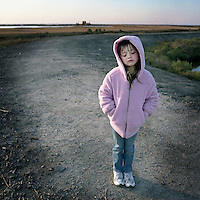 Juliette Brunet stands on the small flood protection levee across the street from her house on Isle Jean Charles, Louisiana. A natural gas pumping station is visible on the horizon. Juliette lost both of her parents when she was younger and is being raised by her uncle who is bound to a wheelchair.