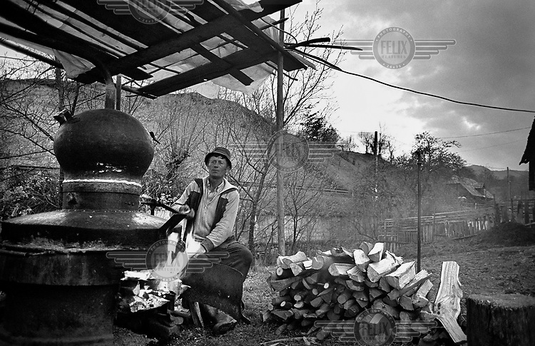 A man makes alcohol in a home made distillery, which makes strong spirits, usually from plums. Maramures.