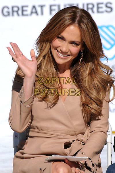 JENNIFER LOPEZ.Denzel Washington Announces Jennifer Lopez as the First Female Spokesperson for the Boys & Girls Club of America held at Nokia Plaza L.A. LIVE, Los Angeles, California, USA, .30th November 2010..half length camel wavy hair beige hand smiling sitting  wrap dress coat waving .CAP/ADM/BP.©Byron Purvis/AdMedia/Capital Pictures.
