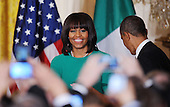 First lady Michelle Obama smiles as President Obama looks on during a reception for the Irish Prime Minister Kenny in the East Room on March 19, 2013 in Washington, DC.<br /> Credit: Olivier Douliery / Pool via CNP