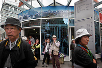 Asian tourists flock to Zermatt  to see  a glimpse of the Matterforn through the fog.