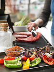 A tray of grilled vegetables and bowl of spice rub in foreground, background is out of focus and shows a person placing steaks on a grill.