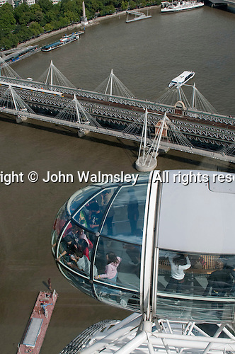 Looking down on Hungerford Bridge, the only bridge to carry both rail and pedestrian traffic across the Thames.  From the highest capsule you can see 40 kilometres.  The London Eye on the Southbank of the River Thames in London.  Stands 135 metres tall and carries 3.5 million visitors each year.  Conceived and designed by David Marks & Julia Barfield, it took 7 years to design & build and involved products made by specialists in 5 countries.   It was originally sponsored by British Airways, who ran it from 2000 until 2005, when it was known as the Millenium Wheel.