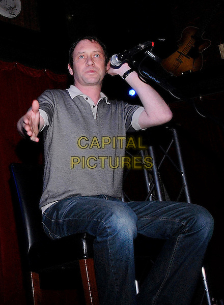OCEAN COLOUR SCENE - SIMON FOWLER.Performing at the Hard Rock Cafe in London, England, March 12th 2009..half length band music playing performing gig concert microphone sitting jeans grey gray t-shirt hand .CAP/IA.©Ian Allis/Capital Pictures