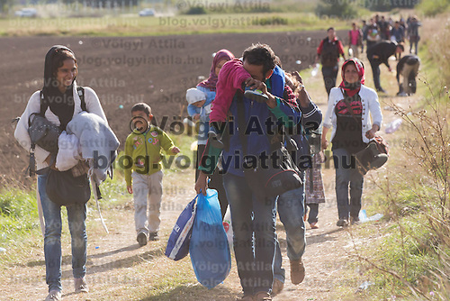 Illegal migrants walk on a dirt road after they crossed the border between Hungary and Serbia near Roszke (about 174 km South of capital city Budapest), Hungary on September 07, 2015. ATTILA VOLGYI