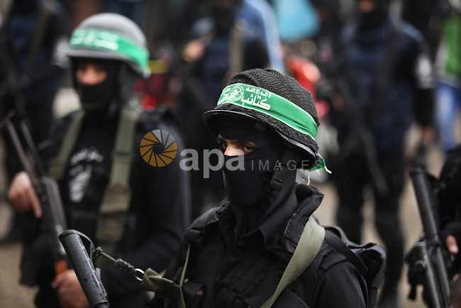 Palestinian members of al-Qassam Brigades, the armed wing of the Hamas movement, hold weapons as they take part in a military parade marking the 27th anniversary of Hamas' founding, in Gaza City December 14, 2014. Photo by Ashraf Amra