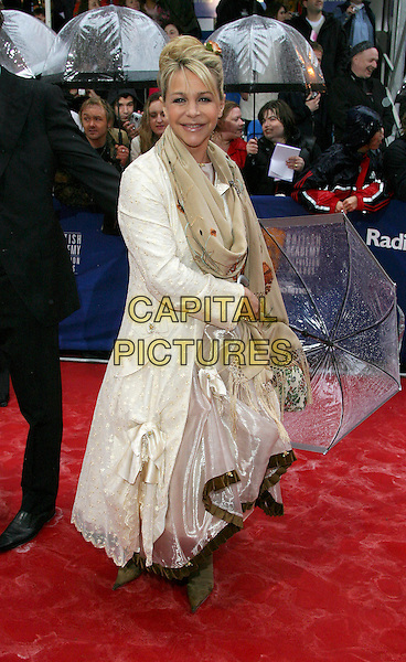 LESLIE ASH.BAFTA TV Awrds, Grosvenor House Hotel, London, .18th April 2004..full length raining wet red carpet umbrella beige cream scarf floral embroidered.Ref: BR.www.capitalpictures.com.sales@capitalpictures.com.©Capital Pictures.