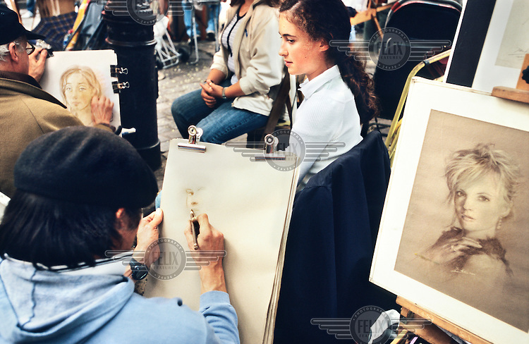 Street artists paint tourists' portraits near the basilica of Montmartre.