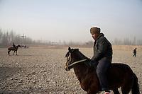 Uighur men ride horses for sale at the Kashgar Sunday Animal Market in Kashgar, Xinjiang, China.