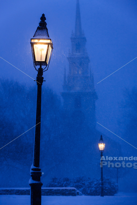 Newport, RI.–Snow falls through the light of an old street lamp with the colonial Trinity Church looming in the blue dusk sky