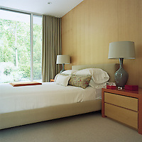 The walls of the guest bedroom are lined with maple and sliding glass doors lead to the garden