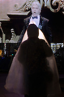 Moscow, Russia, 28/10/2011..A woman wrapped in a plastic sheet against the cold watches the Bolshoi Theatre reopening gala on a giant outdoor video screen in Ploschad Revolutsii. The theatre had been closed since 2005 for reconstruction work that cost some $700 million.