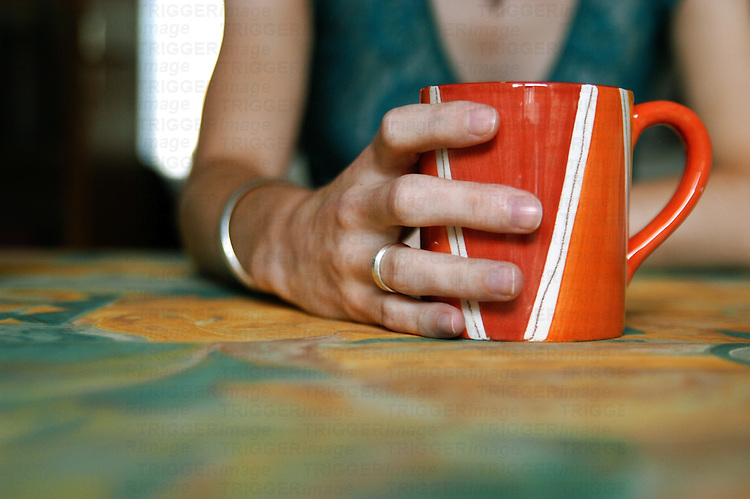 A hand holding a red mug