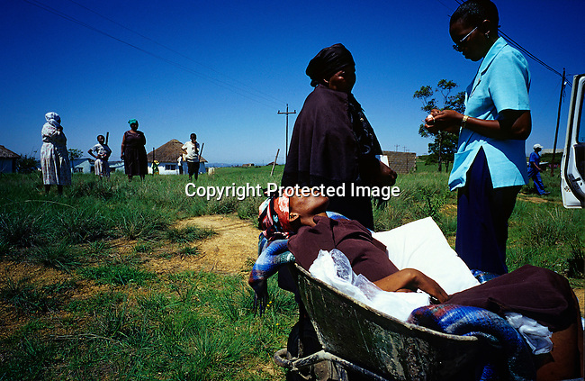 Busisiwe Mfeka, age 28, is dying of Aids and rests in a wheelbarrow, as she is dropped of by a hospice worker with her mother at her side on November 29, 2000 Izingolweni, a rural village in Southern Natal in South Africa. South Africa has one of the highest infection rates of HIV/Aids in the world. It?s estimated that about one thousand people are infected every day and that about 5.5 million people lives with the virus..