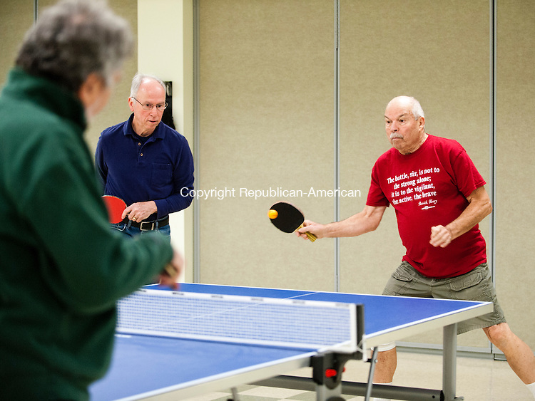 SOUTHBURY, CT-6 January 2015-010615EC02-  Dick Paltauf returns the serve next to his teammate, Will Casazza, as they play table tennis at the Southbury Senior Center Tuesday afternoon. Many of the Southbury seniors, including these men, practice seriously. They are preparing for the Connecticut Masters' Games in April. This year the annual Table Tennis Tournament is in Hartford. Players from all over the state will convene at the Pratt & Whitney gymnasium. Erin Covey Republican-American