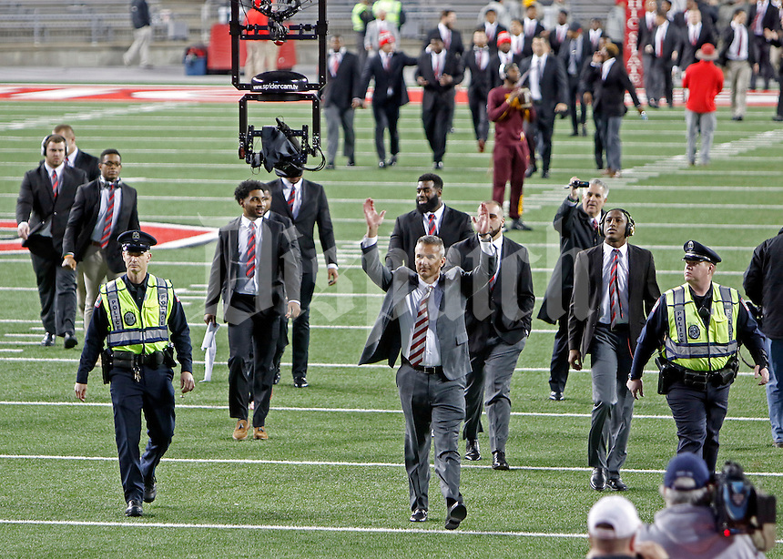 Ohio State Buckeyes head coach Urban Meyer salutes the fans in the block-O section as he enters the Ohio Stadium for the game against the Minnesota Golden Gophers on Saturday, November 7, 2015 in Columbus. (Dispatch photo by Leah Klafczynski)