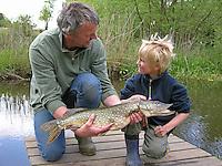 Geangelter Hecht, Angeln, Vater und Sohn freuen sich über ihr Anglerglück, Flusshecht, Flußhecht, Esox lucius, northern pike