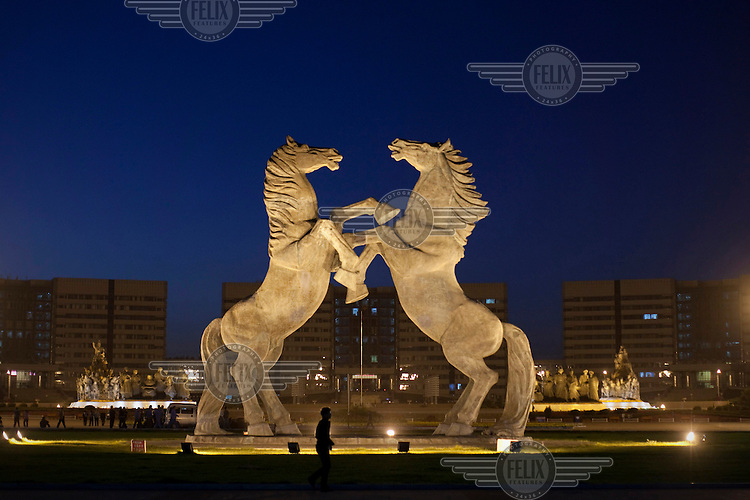 A man walks in front of a giant statue of a pair of rearing horses that stands in front of the government headquarters in Linyinlu Square in the Kangbashi district Ordos. The Kangbashi District of Ordos, a district planned, five years ago, for 1 million inhabitants, still lies almost dormant and has become known as a 'Modern Ghost City.' Yet Ordos has the second largest per capita income after Shanghai, but is ahead of Beijing, largely due to the massive coal wealth of Inner Mongolia.