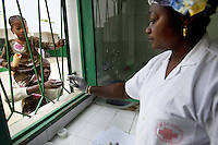 Senegal. Dakar. Hospital Gaspard Kamara ( District sanitaire). The father of a young black girl, suspected tuberculosis (TB) case, gives through a barred window sputum in a plastic sputum cup to Mrs Sarr Rokhaya, a nurse and lab techniciana wearing plastic glove on her hands. The Global Fund supports the tuberculosis (TB) program with a financial grant. 08.12.09  © 2009 Didier Ruef