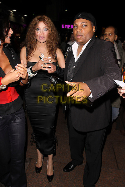 """LA TOYA JACKSON & GUEST.Leaving the UK Premiere of """"The Imaginarium Of Doctor Parnassus"""" at the Empire Leicester Square, London, England.  .October 6th, 2009 .LaToya full length black dress corset lace-up cleavage plastic surgery arm warmers sleeves diamond silver  bracelets suit hat mouth open.CAP/AH.©Adam Houghton/Capital Pictures."""
