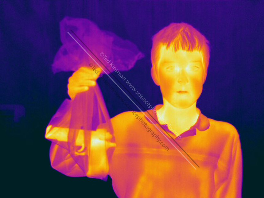 Infrared shows a gun hidden inside a black plastic garbage bag.  A Thermogram of a boy with glasses.  This image is part of a series.  The different colors represent different temperatures on the object. The lightest colors are the hottest temperatures, while the darker colors represent a cooler temperature.  Thermography uses special cameras that can detect light in the far-infrared range of the electromagnetic spectrum (900?14,000 nanometers or 0.9?14 µm) and creates an  image of the objects temperature..