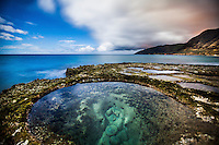 A clear tide pool offers peaceful moments at Yokohama Beach as clouds drift past Ka'ena Point on O'ahu.
