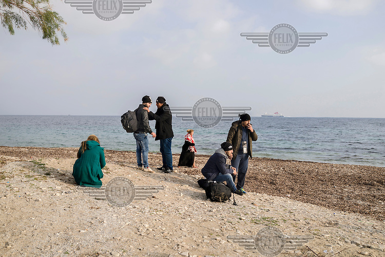 A group of refugees who have just landed gather themselves on the shore following the journey across the Aegean Sea from Turkey.