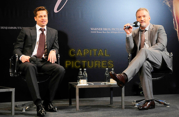 "BRAD PITT & DAVID FINCHER.Press conference for the European premiere of the film ""The Curious Case of Benjamin Button"", Cinestar Sony Center, Berlin, Germany..January 19th, 2009.full length black grey gray brown suit sitting legs crossed microphone .CAP/PPG/NK.©Norbert Kesten/People Picture/Capital Pictures"