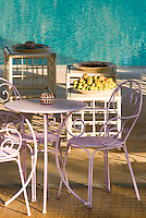The terrace beside the outdoor swimming pool is furnished with a combination of white bamboo side tables and pink wrought iron tables and chairs