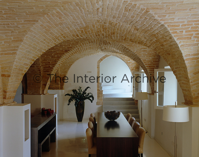 Comfortable upholstered chairs flank the dining table under the brick vaulted ceiling of this cool contemporary dining room