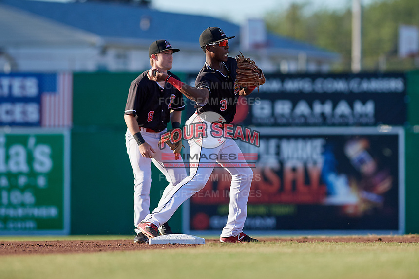 Batavia Muckdogs shortstop Demetrius Sims (3) throws to first base as second baseman Luke Jarvis (8) looks on during a game against the State College Spikes on July 7, 2018 at Dwyer Stadium in Batavia, New York.  State College defeated Batavia 7-4.  (Mike Janes/Four Seam Images)