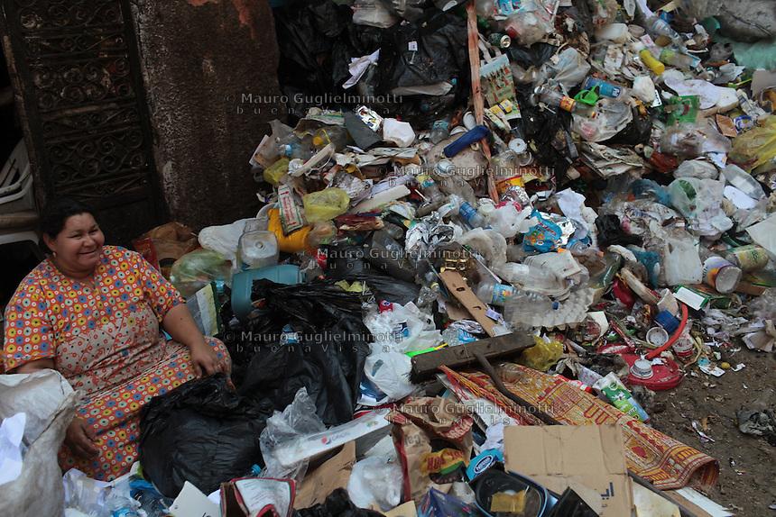2011 Mokattam Garbage City (alla periferia del Cairo) il quartiere copto dove si vive in mezzo alla spazzatura raccolta: una donna robusta seduta in strada a dividere l'immondizia. Accanto a lei una montagna di rifiuti.