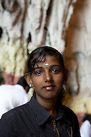 tamile Hindu girl  at Thaipusam ceremonies,  Batu Caves, Kuala Lumpur, Malaysia, 2012. Thaipusam ceremonies, celebrated by tamile Hindu community in Malaysia, take place  in Sanctuary of Batu Caves at the border of Kuala Lumpur, each year around end of January or beginning of February, according to Hindu moon calendar. The event is paying hommage to Lord Murugan, a spirit or god created by Shiva to lead the army of gods against the army of evil demons, finally defeating the evil spirits. There are many ways to present offerings or sacrifices for this major religious event. Devotees mortify their bodies by carrying heavy kavaris with spears fixed in their skin or fruits, flowers and little post with holy milk fixed with hooks in their skin, ascending the stairways to the sanctuary in trance, `followed by assistant  taking care and musicians playing loud and fast rhythmic trance music.  Many families shave their head in a ritual before ascending the stairways, as part of rituals to obtain salvation for their ancestors.